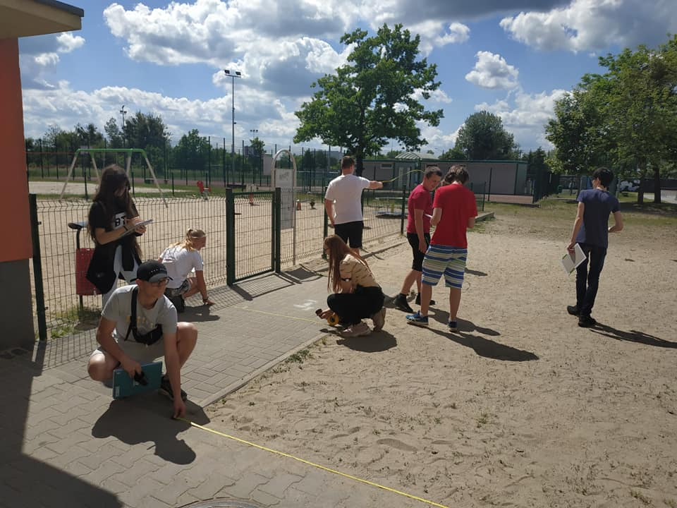 uczniowie przy pomiarach boiska